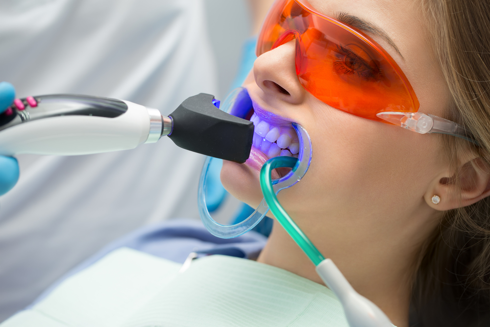 Patient getting teeth whitened at dentist